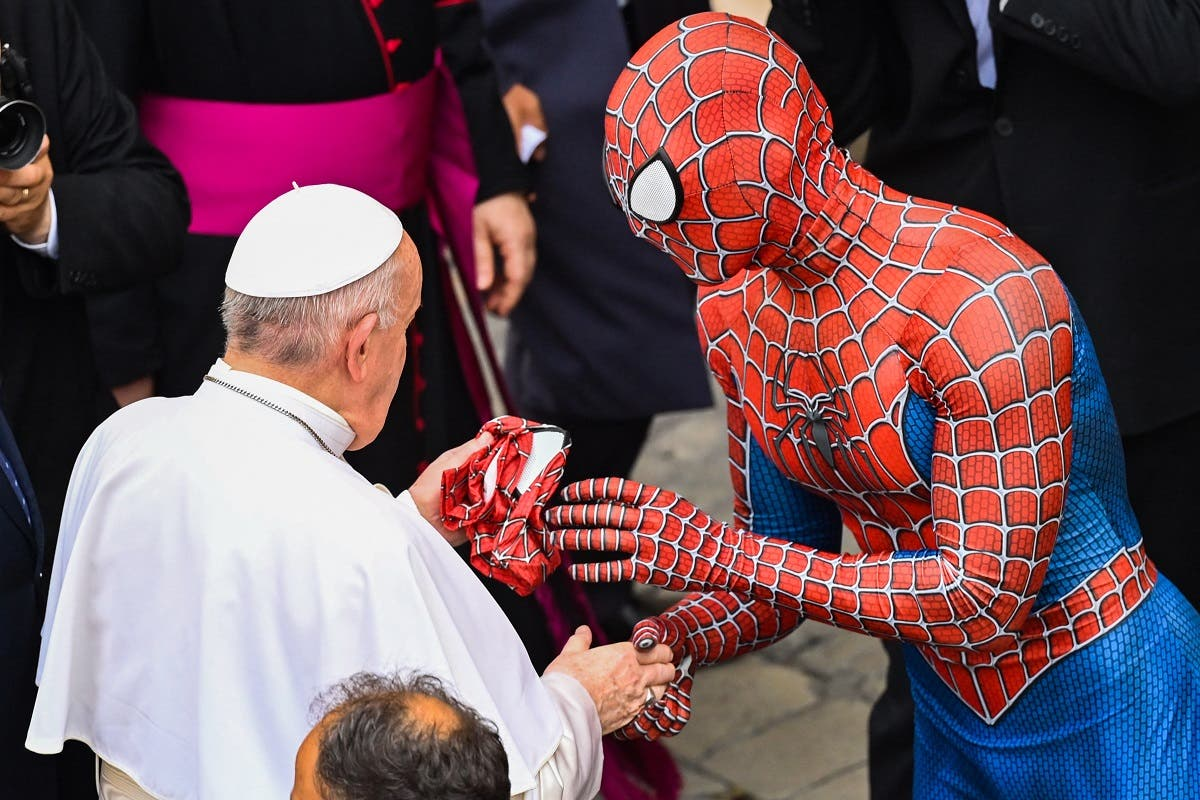 Mattia Villardita who is wearing a costume of the Spider-Man hands a Spider-Man mask to Pope Francis as they meet at the end of the weekly general audience on June 23, 2021 at San Damaso courtyard in The Vatican. (Alberto Pizzoli/AFP)