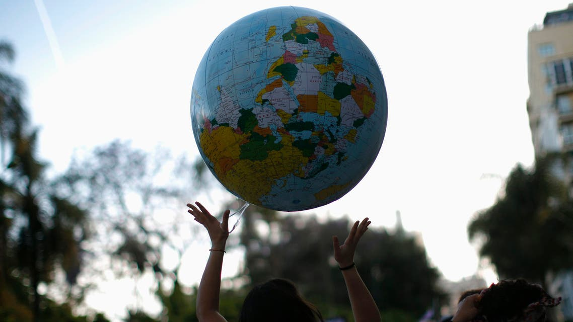 Ana Navarro, 33, plays with a giant inflatable balloon of planet Earth as she takes to the streets during a protest march marking the first year anniversary of Spain's Indignados (Indignant) movement in Malaga, southern Spain May 12, 2012. (Reuters)
