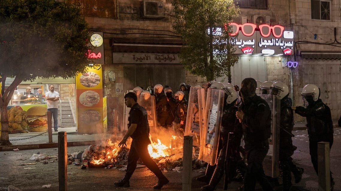 Angry demonstrators set fires, block the streets of the city center and clash with riot police following the death of Nizar Banat, an outspoken critic of the Palestinian Authority, in the West Bank city of Ramallah, on June 24, 2021. (AP)