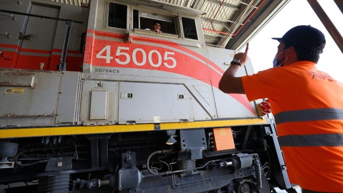 A picture taken on April 1, 2021 shows employees working in the main waggon of a train of the Etihad Rail network, in al-Mirfa, in the United Arab Emirates. (AFP)