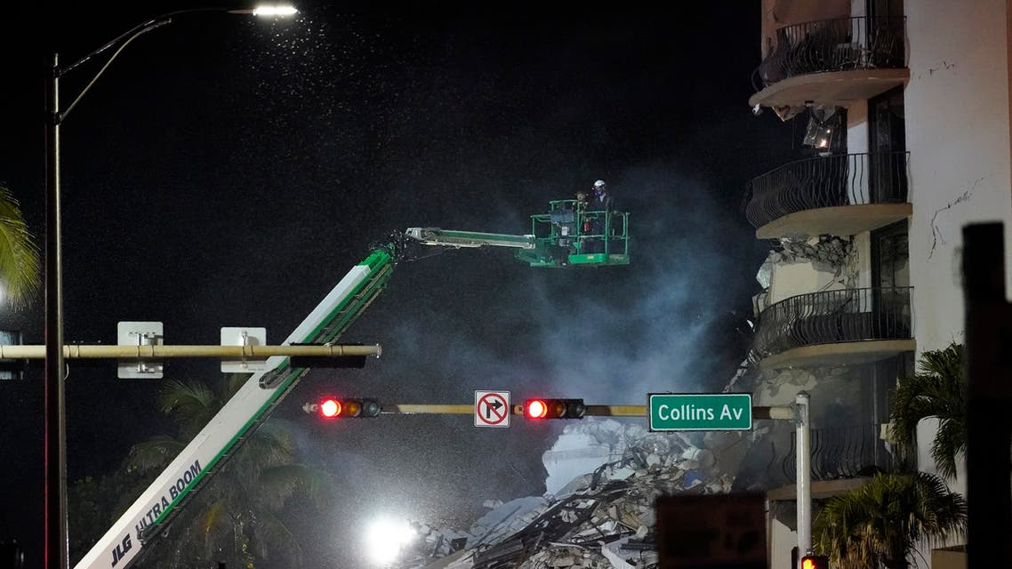 Workers ride in a lift as smoke rises off the rubble where a wing of a 12-story beachfront condo building collapsed, late on Thursday, June 24, 2021, in the Surfside area of Miami. (AP)