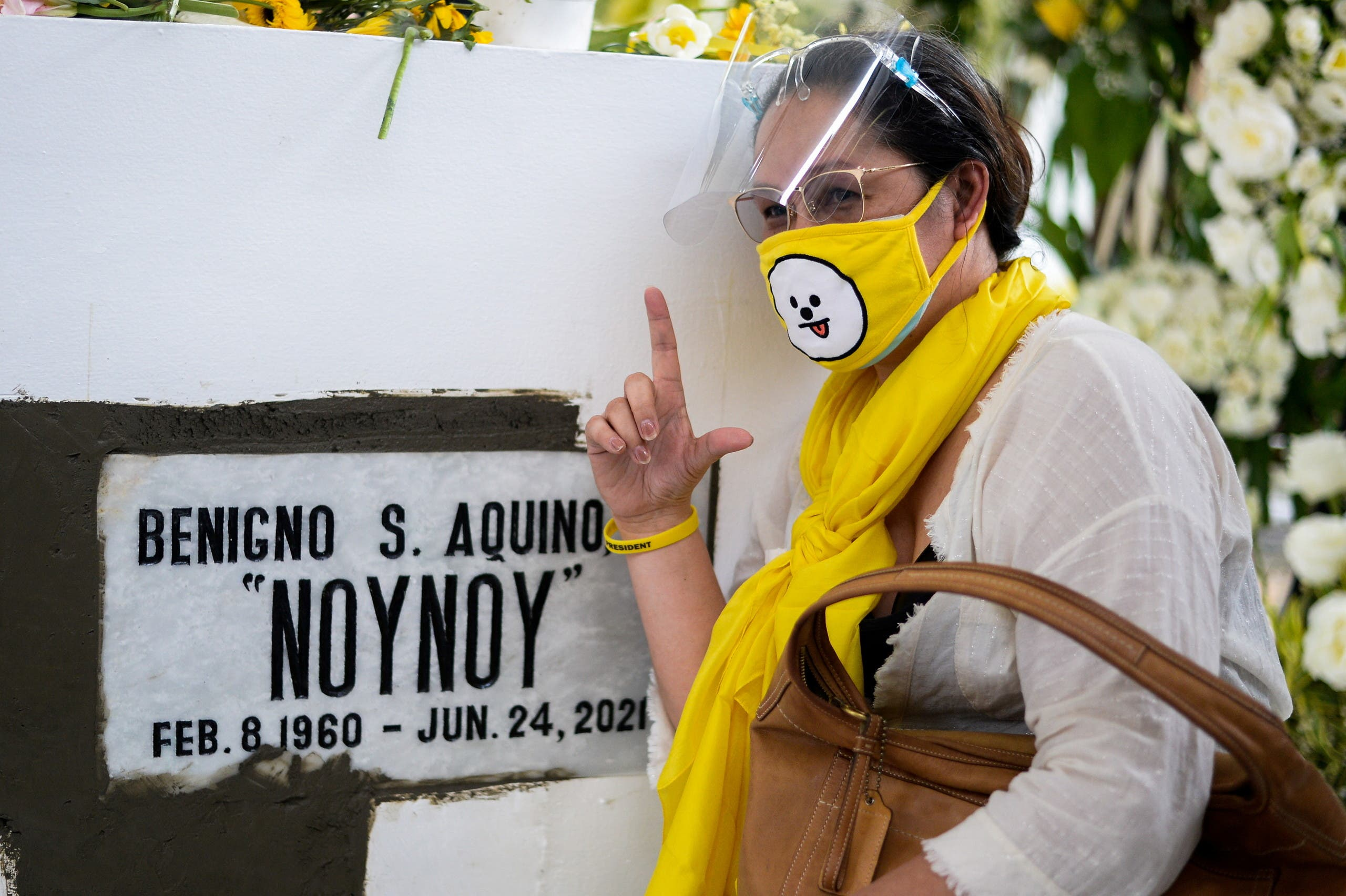 A woman flashes the 'L' sign for the Filipino word laban which means fight, following the burial of Philippine President Benigno Aquino III, at the Manila Memorial Park, in Paranaque city, Metro Manila, Philippines, June 26, 2021. (Reuters)