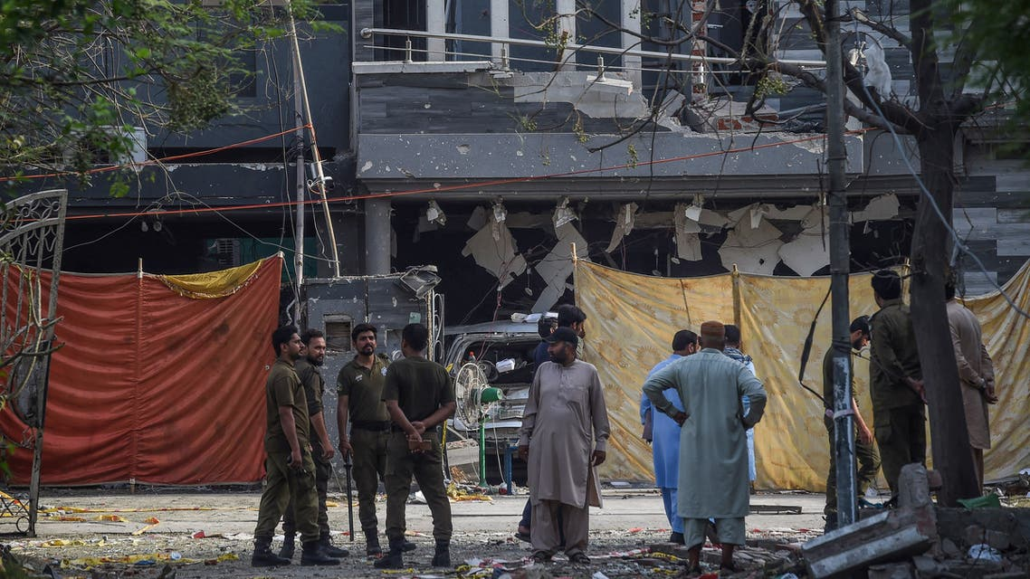 Police and locals stand near the site of an explosion in Lahore on June 24, 2021 a day after a car bomb killed three people in the Pakistan's eastern megacity. (AFP)
