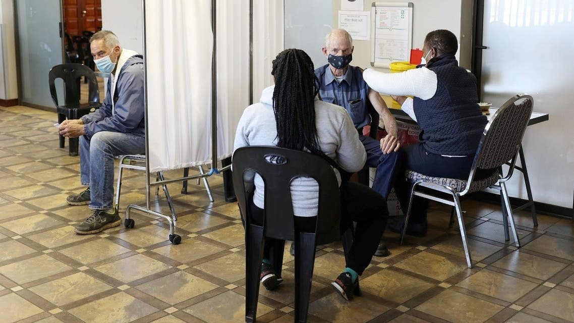 A man is vaccinated as another looks on while waiting to receive a dose of a coronavirus disease vaccine in Meyerton, south of Johannesburg, South Africa June 23, 2021. (Reuters/Siphiwe Sibeko)