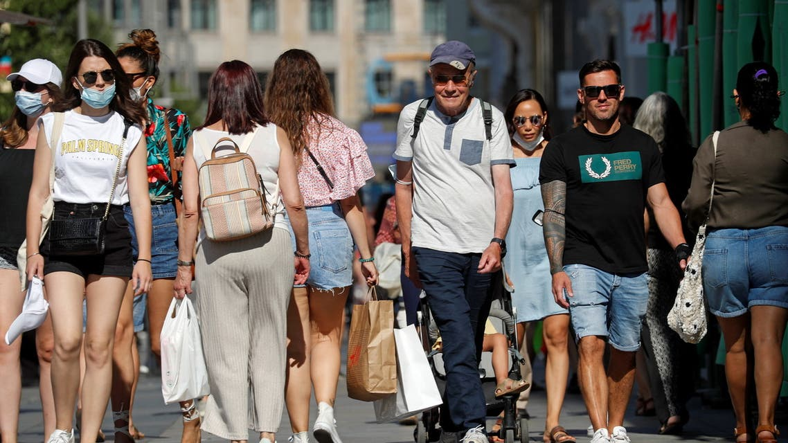 People, some without protective masks, walk downtown Madrid, as they are no longer required outdoors from June 26, amid the coronavirus disease (COVID-19) pandemic, Spain, June 26, 2021. (Reuters)