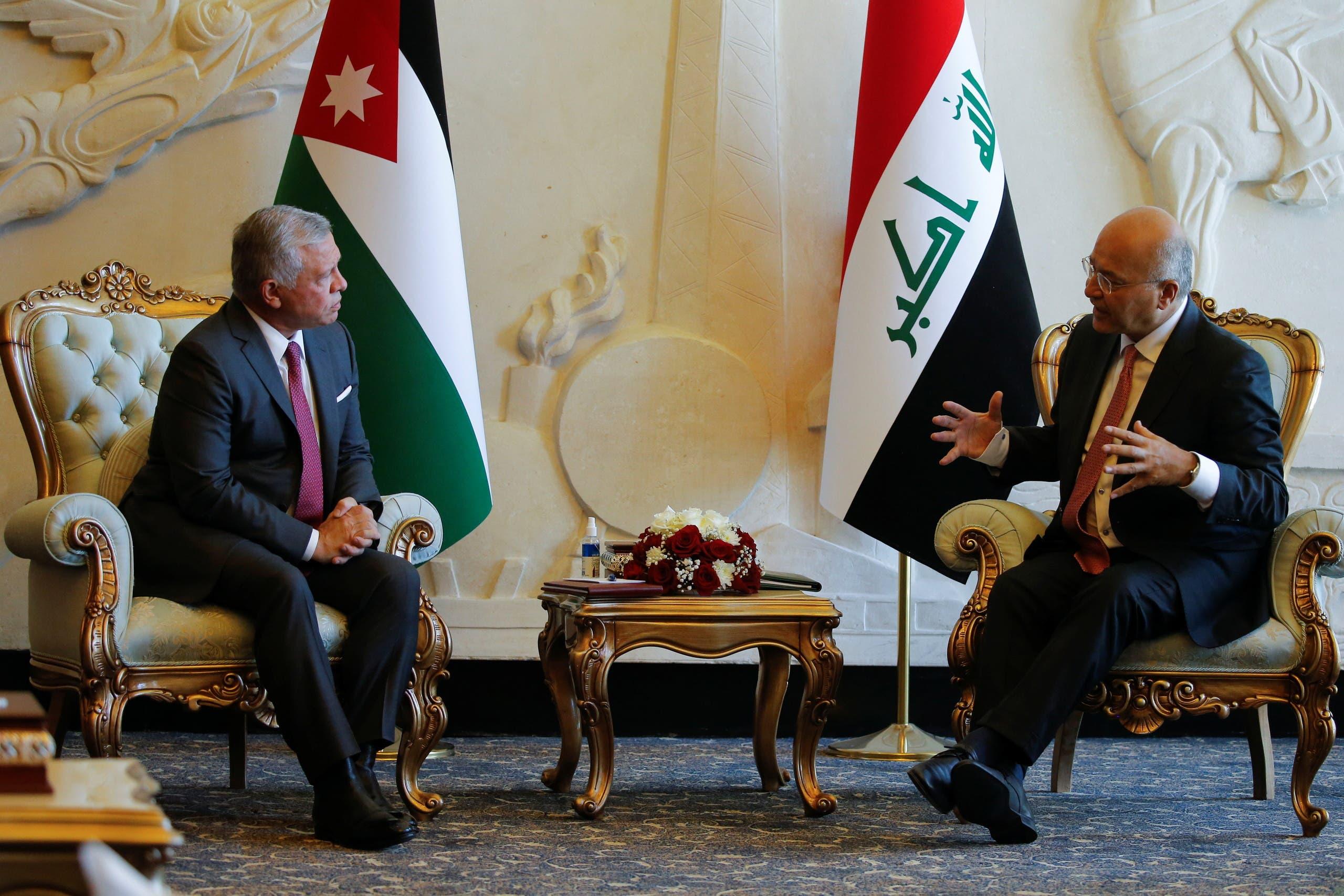 Iraqi President Barham Salih and King Abdullah II of Jordan talk at Baghdad International Airport in Baghdad, Iraq June 27, 2021. (Reuters)