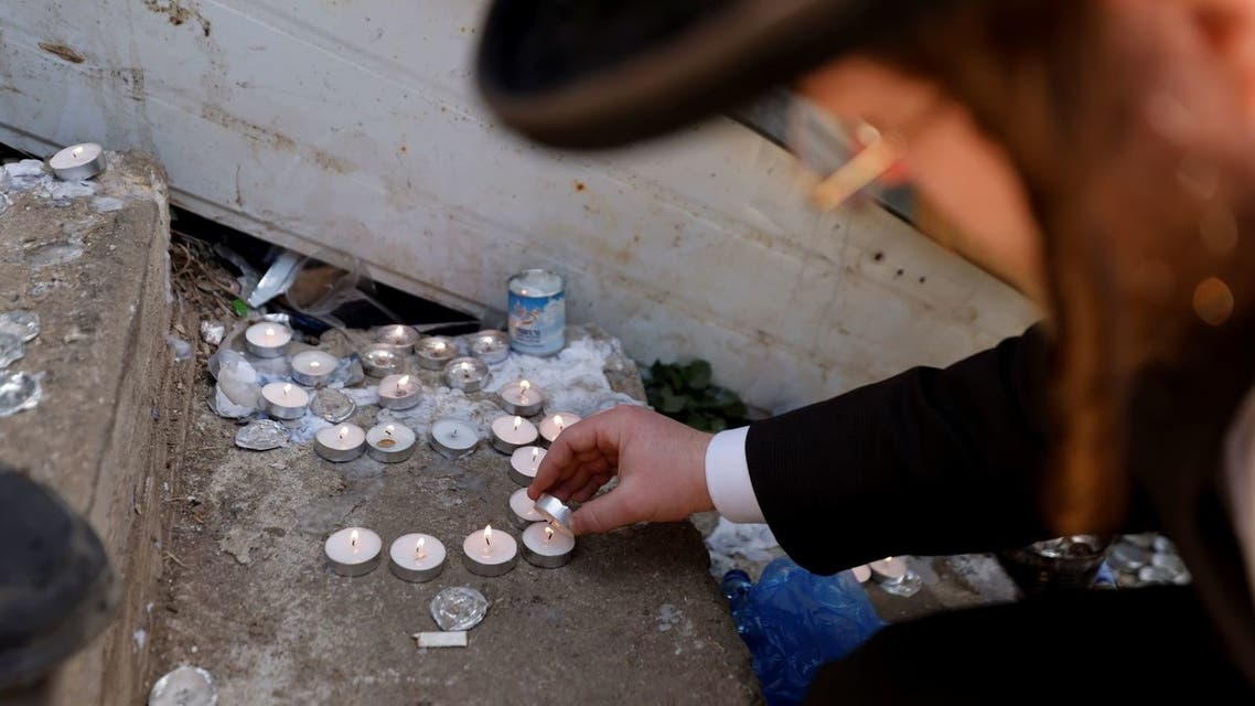 An ultra-Orthodox Jewish man lights candles at the site where dozens were crushed to death in a stampede at a religious festival, as the country observes a day of mourning, at Mount Meron, Israel May 2, 2021. (Reuters)
