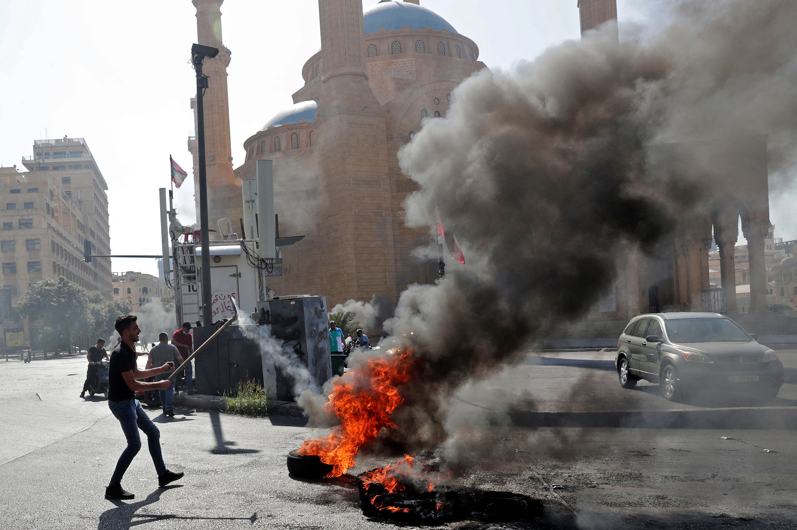 Demonstrators burn tires to block the Martyrs' Square in the centre of Lebanon's capital Beirut on June 26, 2021, as they protest against dire living conditions amidst the ongoing economical and political crisis. (AFP)