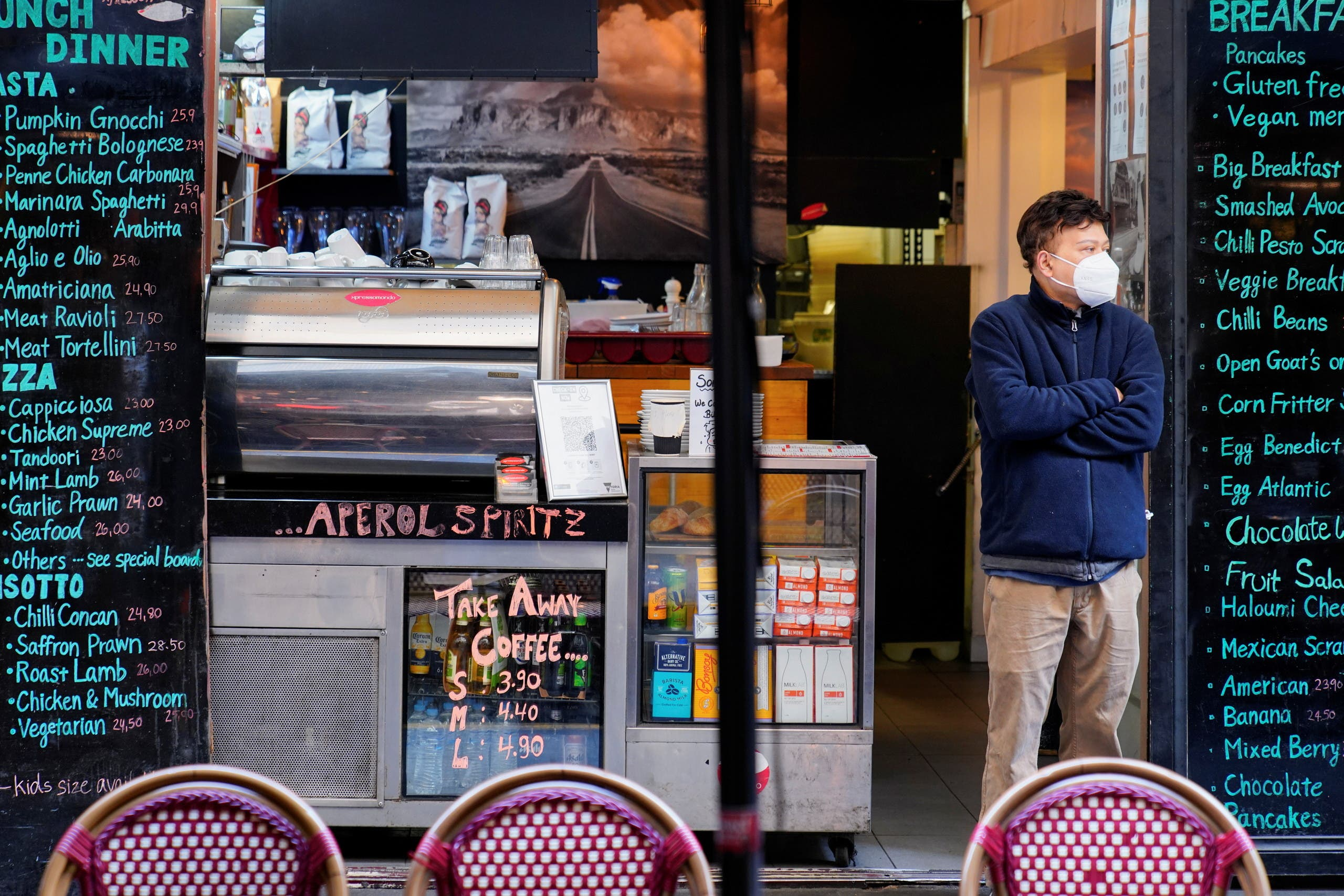 A man wearing a protective face mask stands at the entrance of a cafe on the first day of eased coronavirus disease (COVID-19) restrictions for the state of Victoria following an extended lockdown in Melbourne, Australia, June 11, 2021. (Reuters)