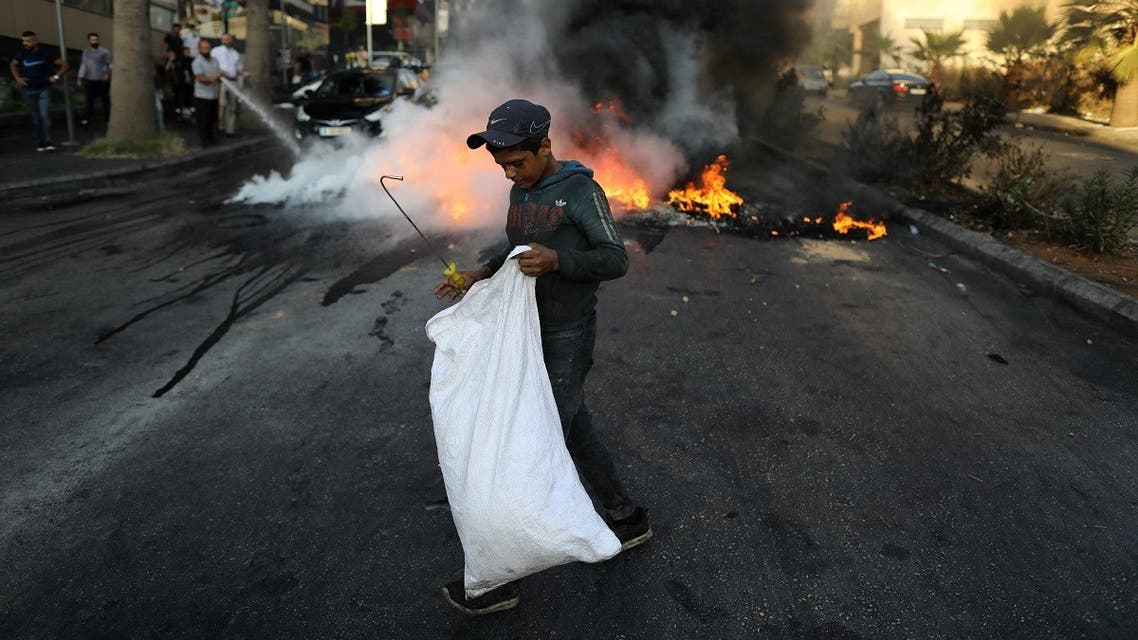 A Lebanese boy collects items from the street near tires set on fire during a protest at a main road in Lebanon's capital Beirut against dire living conditions amidst the ongoing economical and political crisis, on June 28, 2021. (AFP)