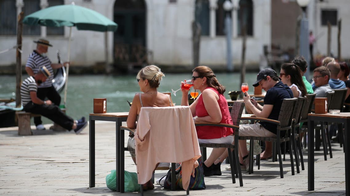 People enjoy a drink at a restaurant, as the region of Veneto becomes a white zone, following a relaxation of COVID-19 restrictions with only masks and social distancing required, in Venice, Italy, June 7, 2021. (Reuters)