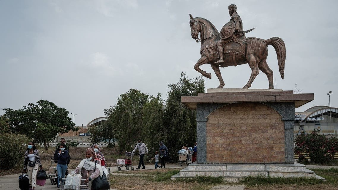 Passengers walk next to the statue of Alula Aba Nega, Ethiopian general from Tigray, after flights to Addis Ababa was cancelled at Mekelle airport in Mekele, the capital of Tigray region, Ethiopia, on June 25, 2021. (AFP)
