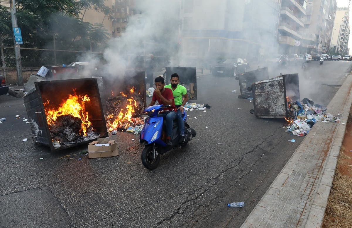 Two men ride past burning garbage bins during a protest at a main road in Lebanon's capital Beirut against dire living conditions amidst the ongoing economical and political crisis on June 28, 2021. (AFP)