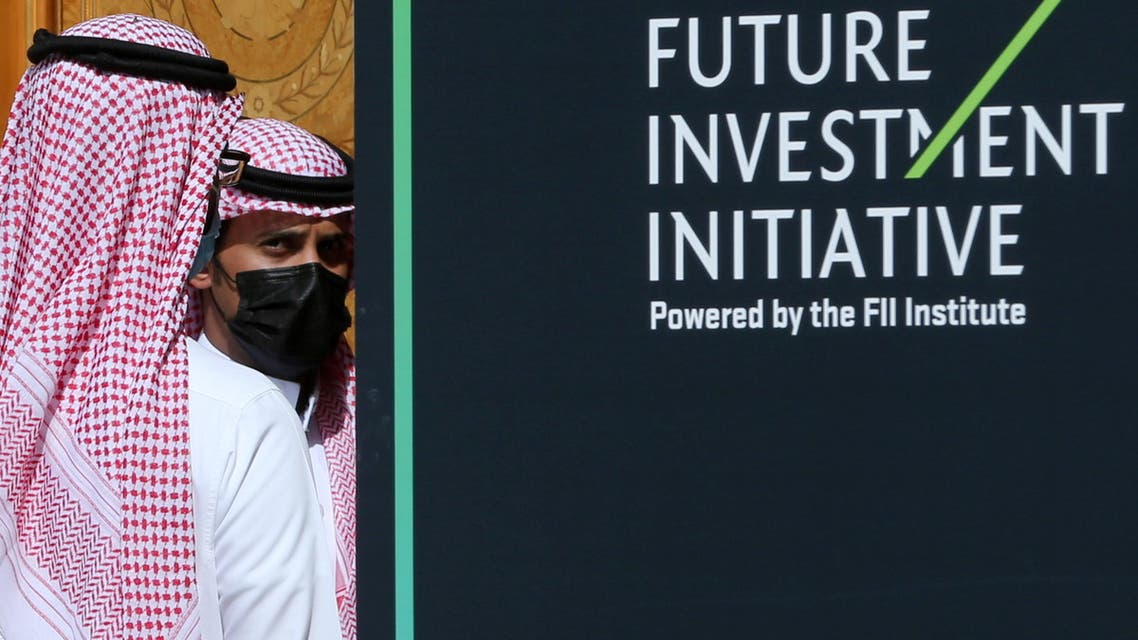 Saudi men are seen next to a logo of the Future Investment Initiative ahead of the opening ceremony of the fourth annual conference in Riyadh, Saudi Arabia January 27, 2021. (Reuters)