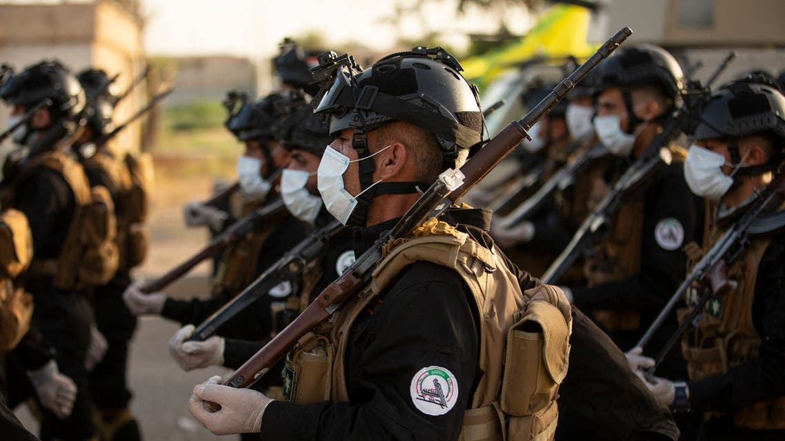In this file photo taken on June 14, 2020 Mask-clad members of the Hashed al-Shaabi (Popular Mobilisation) paramilitary force take part in a military parade in the southern Iraqi city of Basra. (AFP)
