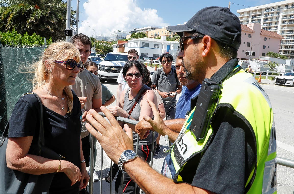 Family members of those reported missing ask Joseph Dahan (R), an EMT with Hatzalah, a volunteer emergency organization, on how to join other families to view the site of a partially collapsed residential building in Surfside, near Miami Beach, Florida, U.S. June 27, 2021. (Reuters)
