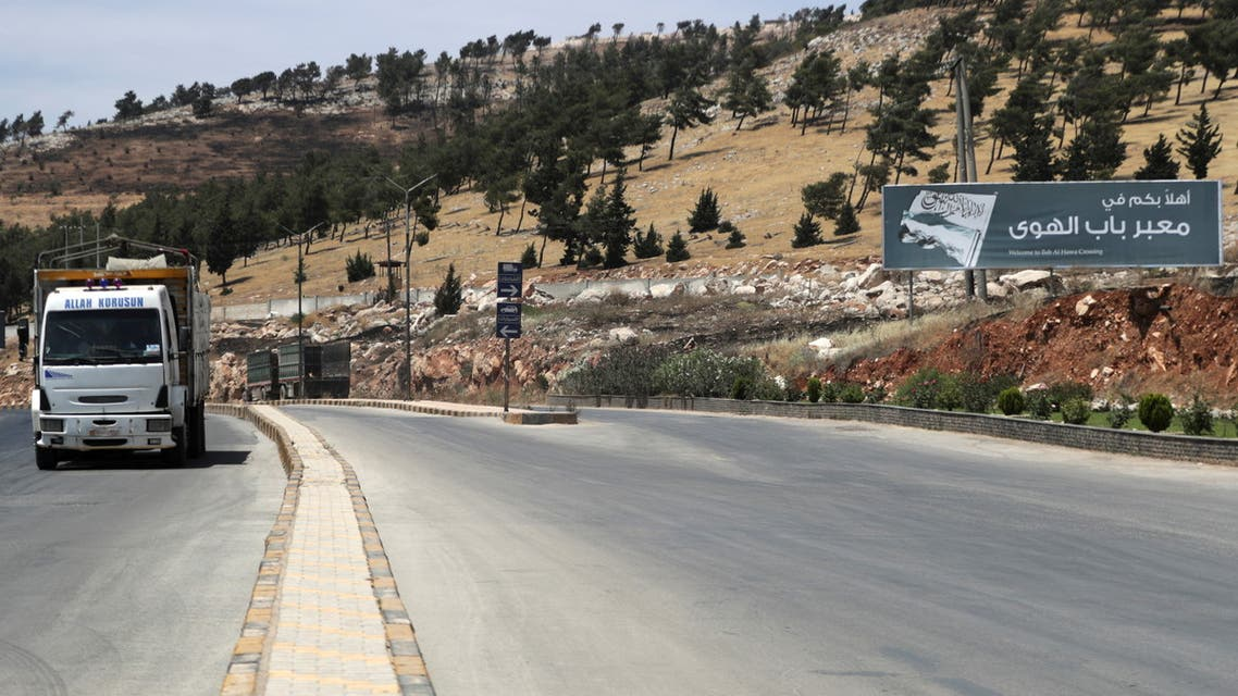 A vehicle drives past a road sign that reads Welcome to Bab al-Hawa crossing, at Bab al-Hawa crossing at the Syrian-Turkish border, in Idlib governorate, Syria June 10, 2021. Picture taken June 10, 2021. REUTERS/Khalil Ashawi