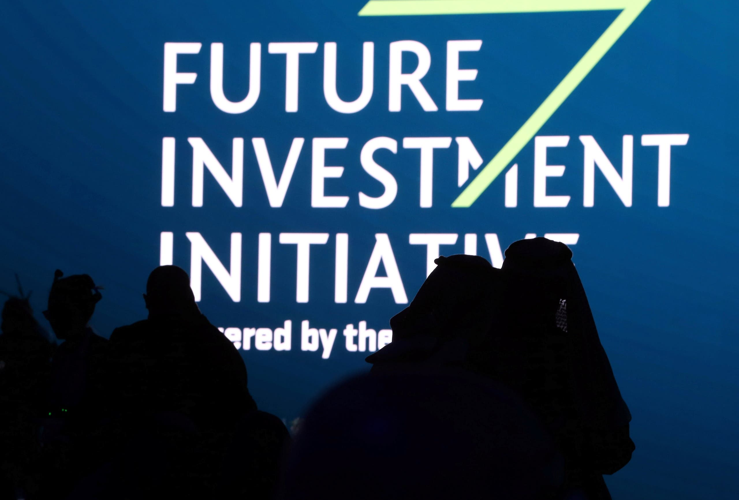 Silhouettes of Saudi men are seen during the opening ceremony of the fourth annual Future Investment Initiative in Riyadh, Saudi Arabia, January 27, 2021. (Reuters)
