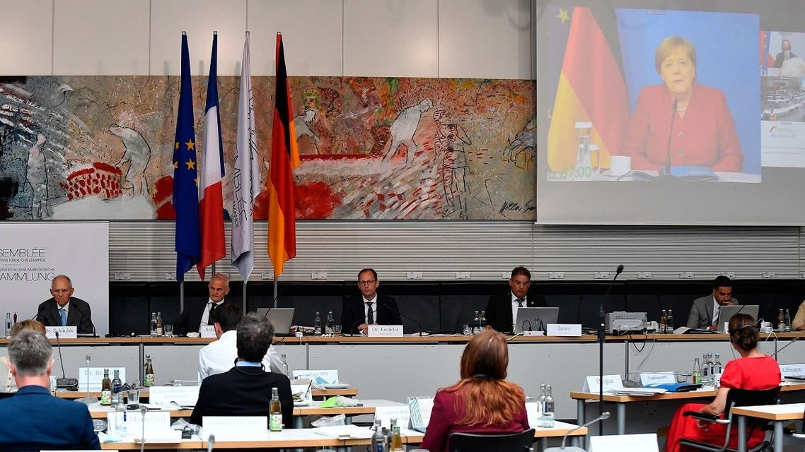 German Chancellor Angela Merkel and French Prime Minister Jean Castex (top, R) are displayed on a screen during a Franco-German Parliamentary Assembly in Berlin on June 28, 2021. (Tobias Schwarz/AFP)