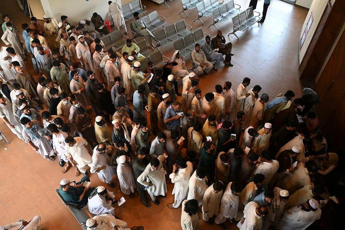 People including overseas Pakistani workers who want to fly to the Middle East stand in a queue to register before receiving a dose of the Pfizer Covid-19 vaccine at a vaccination center in Islamabad on June 28, 2021. (AFP)