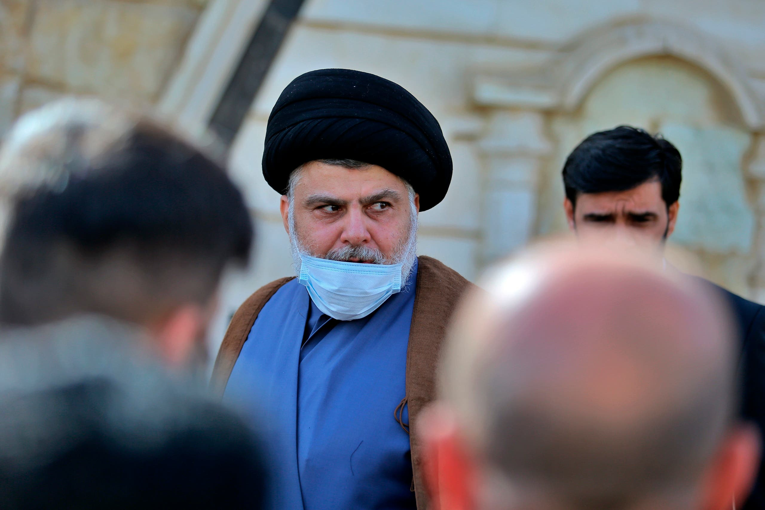Muqtada al-Sadr, center, leaves a news conference in Najaf, Iraq, Wednesday, Feb. 10, 2021. (AP)