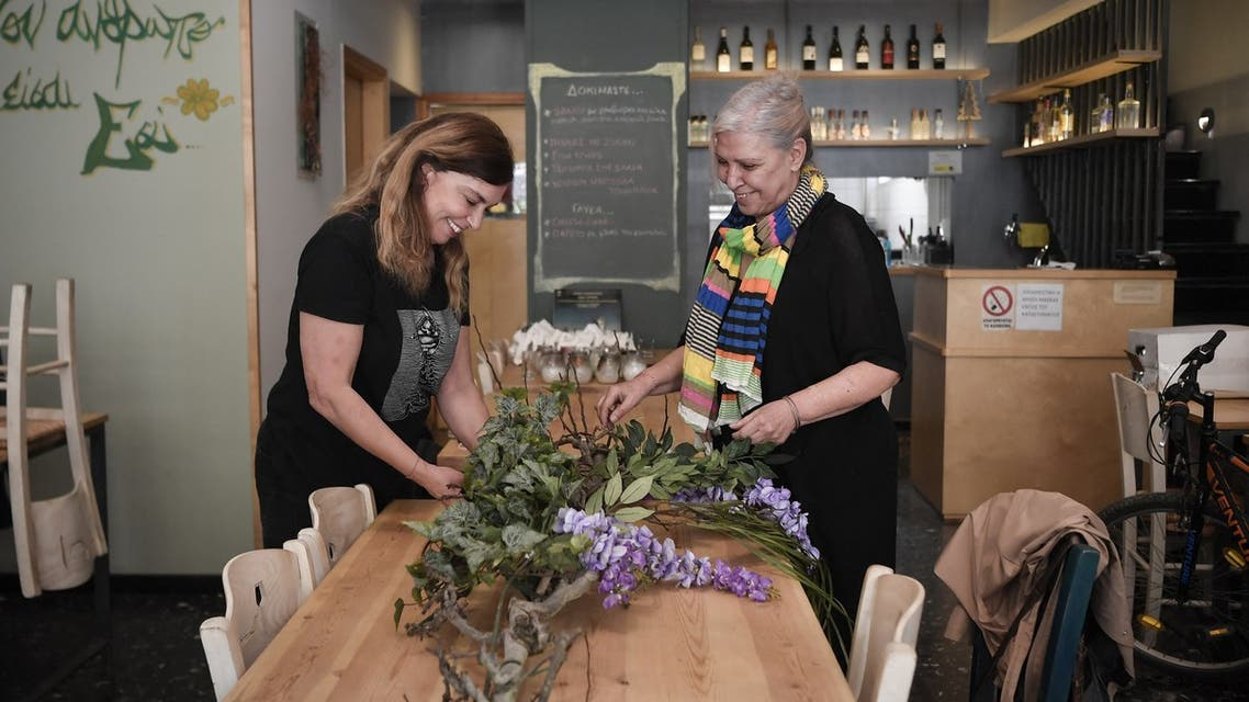 Venetia, owner of a restaurant and her cook Florentia arrange flowers to decorate the restaurant, closed since November 2020, in the trendy Koukaki district of Athens on April 6, 2021. (File photo: AFP)