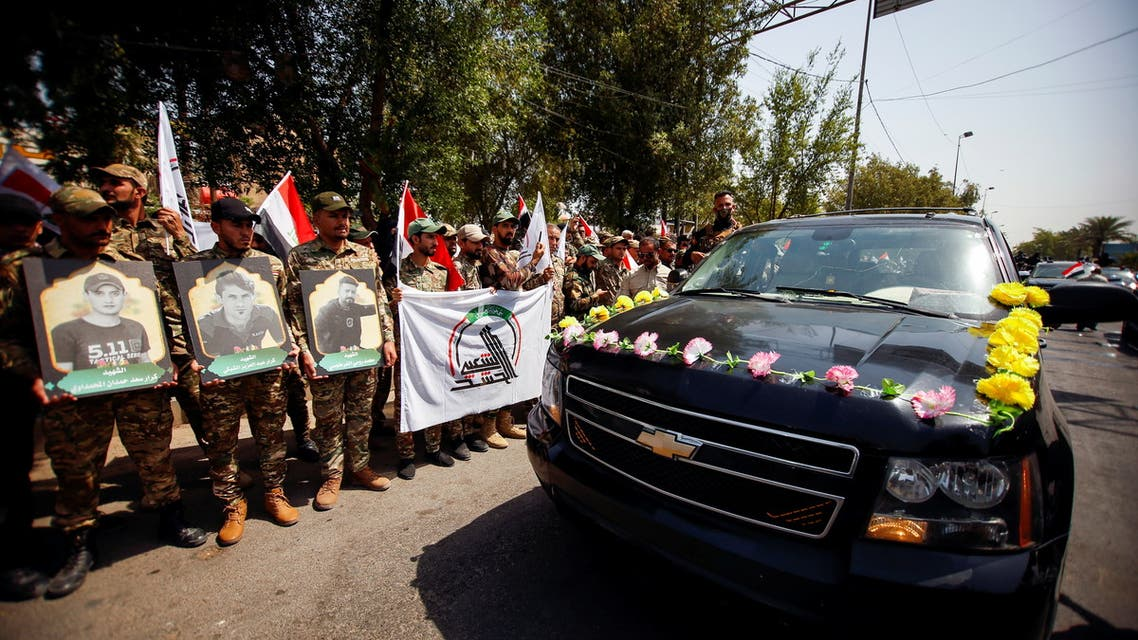 Members of Iraqi Popular Mobilization Forces (PMF) carry pictures of fellow members of PMF, who were killed by U.S. air strikes on the Syria-Iraq border, during a symbolic funeral in Baghdad, Iraq, June 29, 2021. (Reuters)