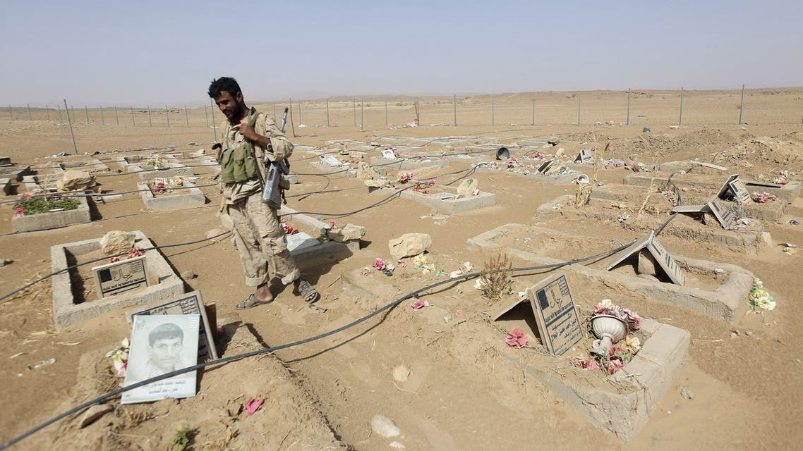 An army soldier stands next to graves of Houthi fighters in the historical town of Baraqish in Yemen's al-Jawf province after it was taken over by pro-government forces from Houthi fighters April 6, 2016. REUTERS/Ali Owidha TPX IMAGES OF THE DAY