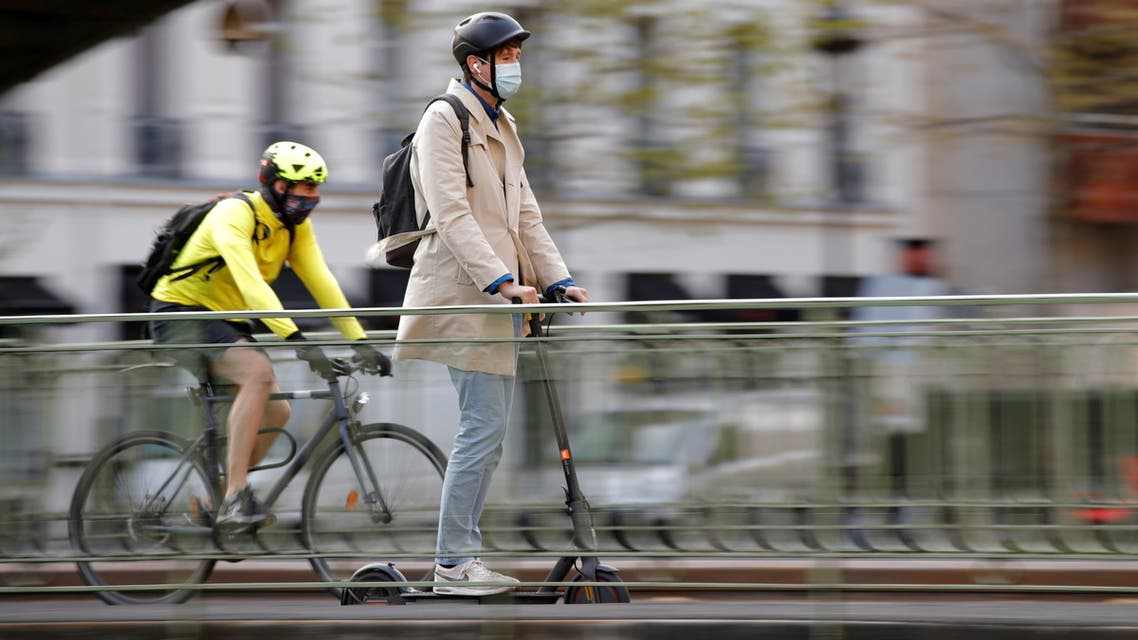 A man, wearing a protective face mask, rides a scooter past a biker on a bridge over the canal Saint-Martin in Paris amid the coronavirus (COVID-19) outbreak in France, April 22, 2021. (Reuters)