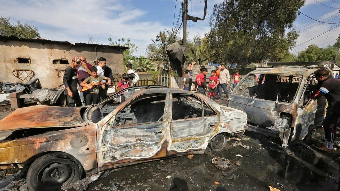 People gather around destroyed vehicles at the scene of an explosion in the Habibiya district of the Sadr City suburb of Iraq's capital Baghdad on April 15, 2021. (AFP)