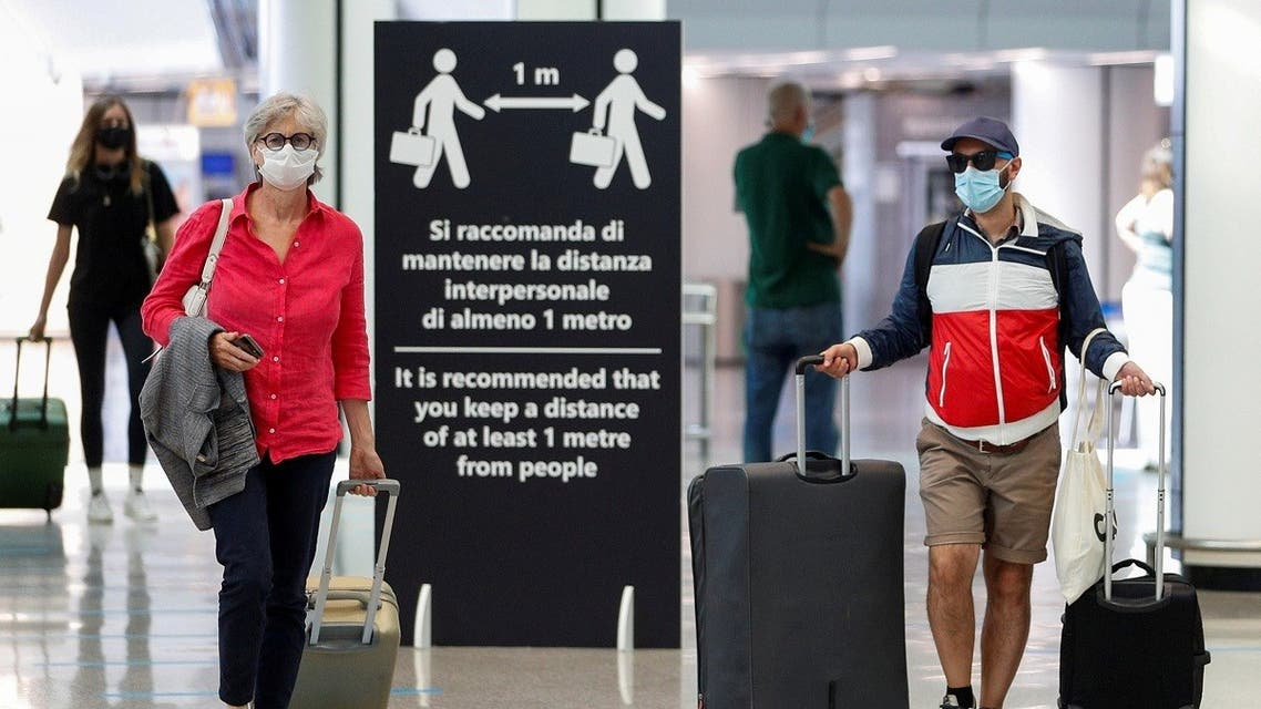 Passengers wearing protective face masks walk at Fiumicino Airport in Rome, Italy, June 30, 2020. (Reuters/Guglielmo Mangiapane)