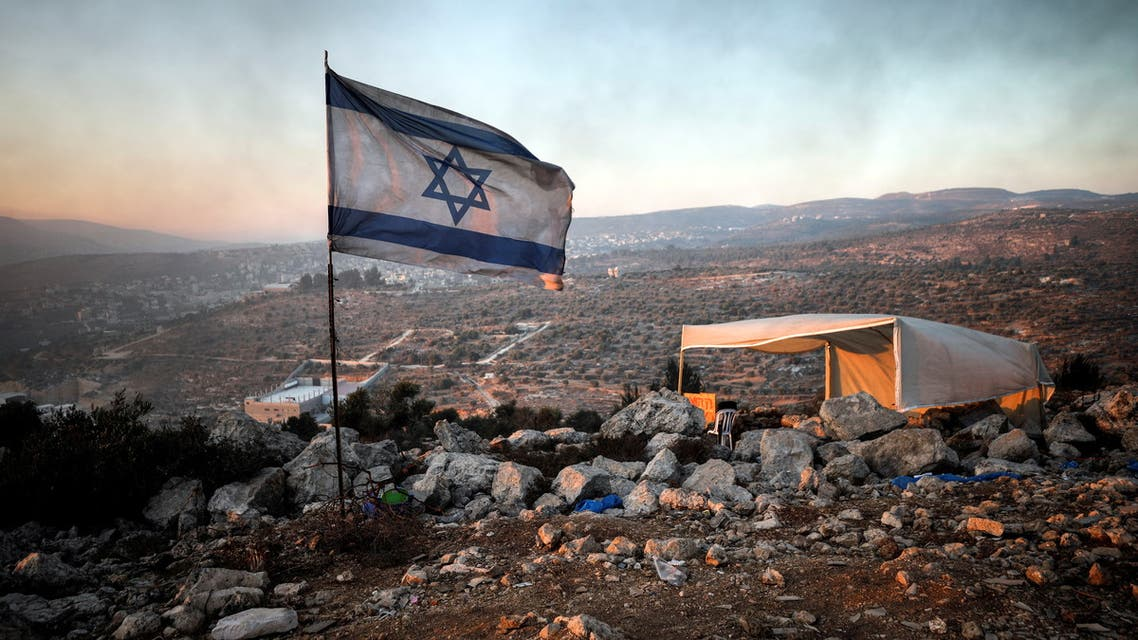 An Israeli flag flutters as smoke from fires lit in the nearby Palestinian village of Beita drifts past it, in Givat Eviatar, a new Israeli settler outpost in the Israeli-occupied West Bank June 23, 2021. Picture taken June 23, 2021. (Reuters)