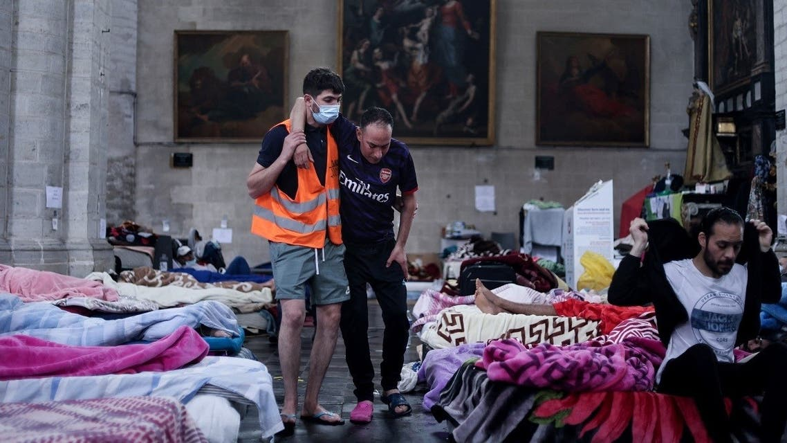 A paramedic volunteer helps a migrant on a hunger strike, occupying the Saint-Jean-Baptiste-au-Beguinage church in Brussels on June 30, 2021. (Kenzo Tribouillard/AFP)