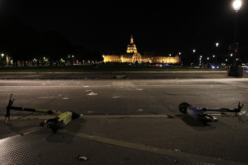 Broken glass and e-scooters are seen on a street in front of Les Invalides in Paris late on June 11, 2021, after people gathered there for an unauthorized outdoor party. (AFP)