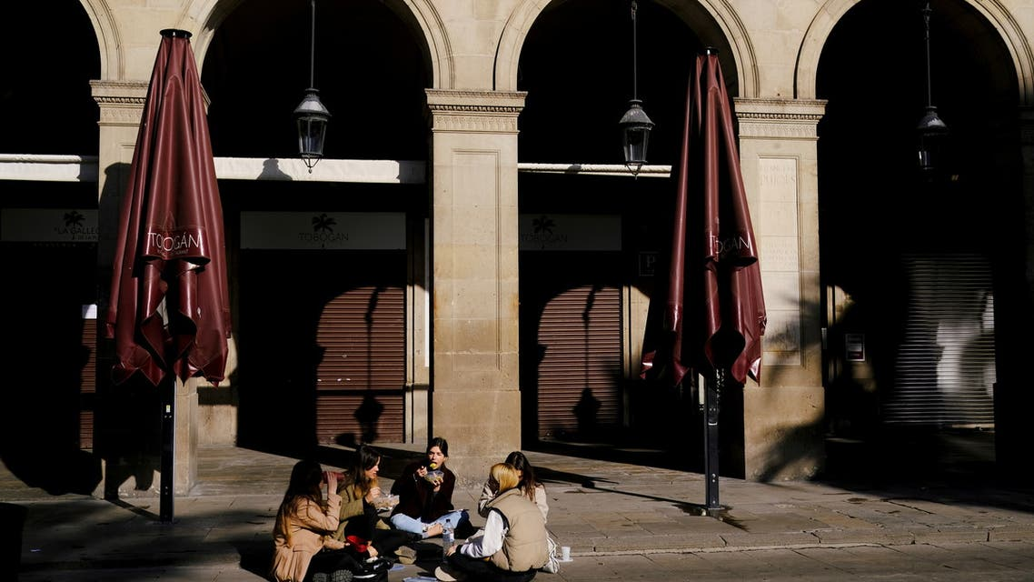 Women eat while sitting in front of a closed restaurant at the empty Plaza Reial (Reial square), after Catalonia's government imposed new restrictions in an effort to control the spread of the coronavirus disease (COVID-19), in Barcelona, Spain January 26, 2021. REUTERS/Nacho Doce