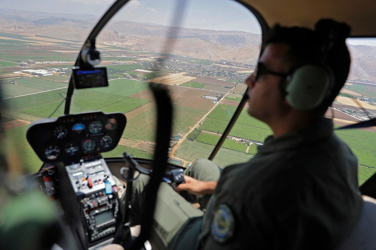 Journalists are given a press tour in a Lebanese Air Force Robinson R44 Raven II taking off from Rayaq military air base to Zahle in the Bekaa Valley on July 1, 2021. (AFP)