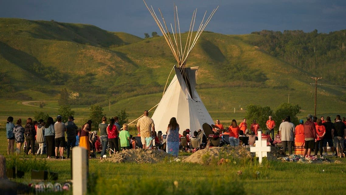 People gather for a vigil in a field where human remains were discovered in unmarked graves at the site of the former Marieval Indian Residential School, June 26, 2021. (AFP)