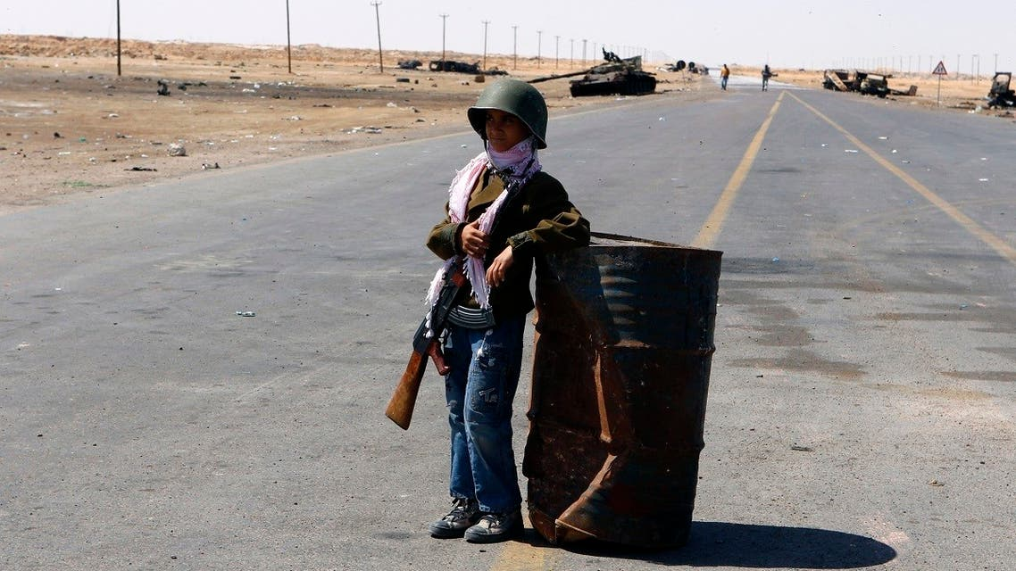 A 10-year-old child stands guard at the frontline along the western entrance of Ajdabiyah. (File Photo: Reuters)