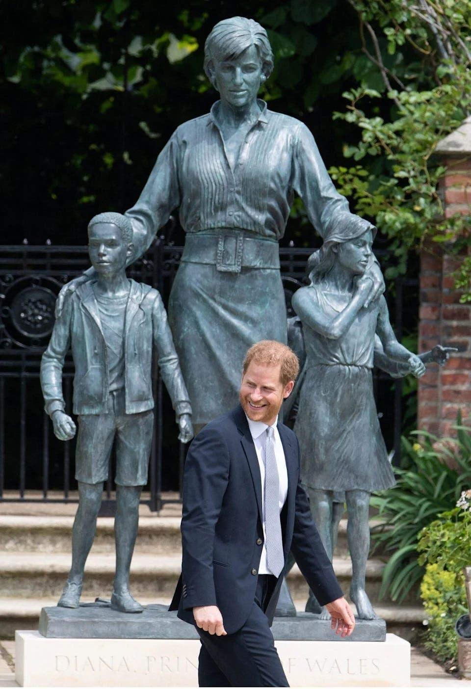 El príncipe Harry sonriendo frente a la estatua.