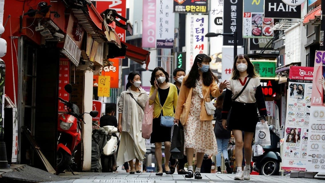 People wearing masks walk at Myeongdong shopping district amid social distancing measures to avoid the spread of the coronavirus disease, in Seoul, South Korea. (Reuters)