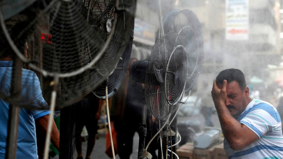 A man stands by fans spraying air mixed with water vapour deployed by donors to cool down pedestrians along a street in Iraq's capital Baghdad on June 30, 2021 amidst a severe heat wave. (AFP)