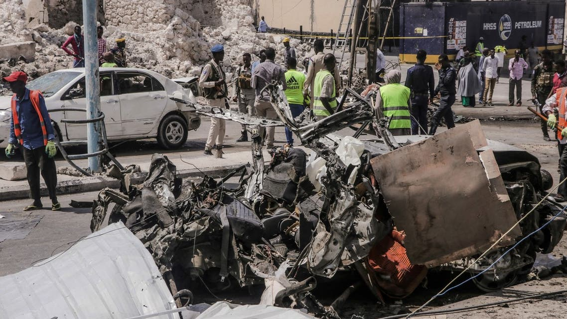 Rescue personnel and bystanders gather near debris at the site of a suicide car bombing attack near a security checkpoint in Mogadishu on February 13, 2021. Three people were killed and eight wounded after a car bomb detonated near a security checkpoint in the Somali capital Mogadishu, a security official and witnesses said.