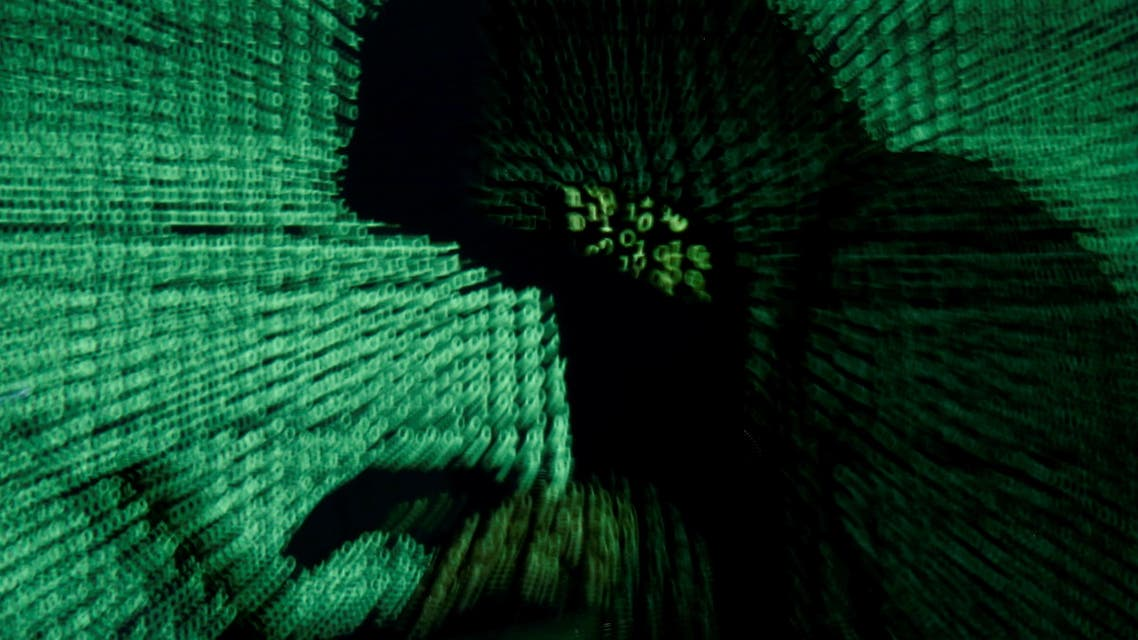 A man holds a laptop computer as cyber code is projected on him in this illustration picture taken on May 13, 2017. (File photo: Reuters)