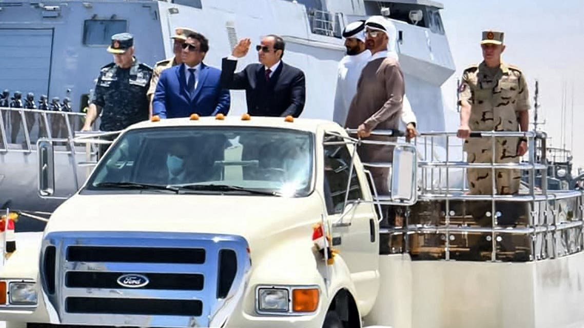 Egypt's President Sisi (C), accompanied by Abu Dhabi Crown Prince Sheikh Mohammed bin (R), riding in a vehicle next to a warship during the inauguration of the naval base in Gargoub on July 3, 2021, in Egypt's northwestern Mediterranean coastal city of Masra Matruh. (Egyptian Presidency/AFP)
