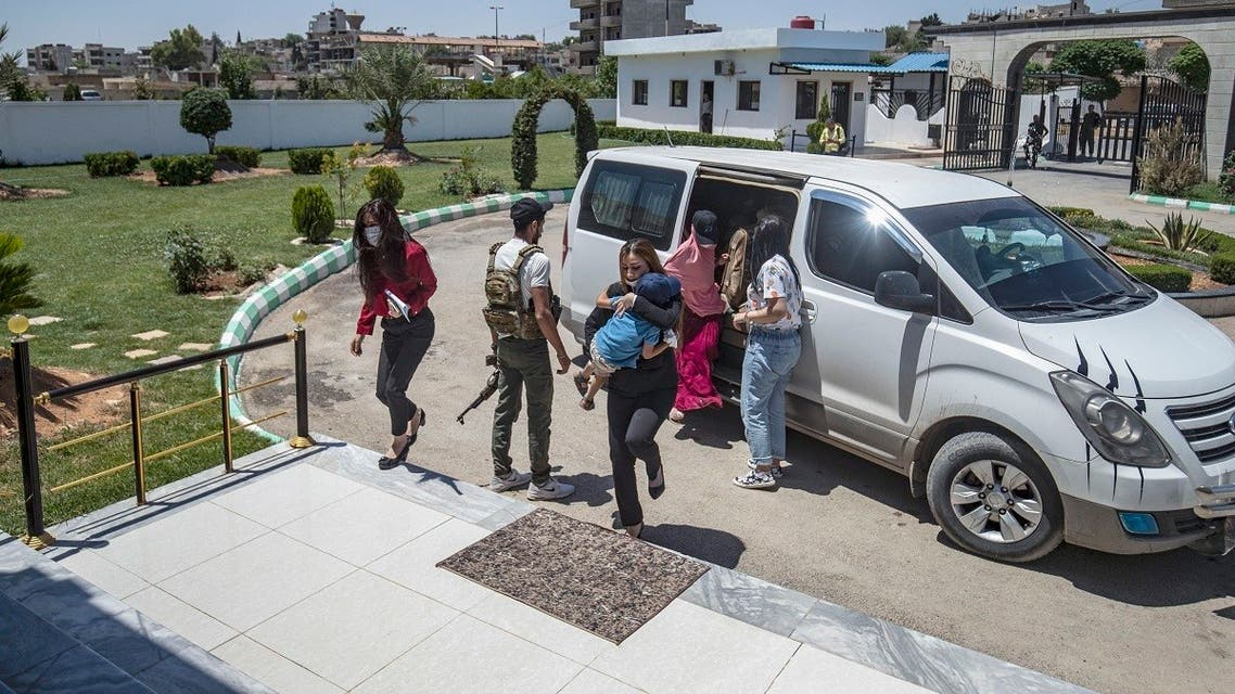 Members of Kurdish security forces accompany relatives of ISIS fighters, before handing them over to a delegation of Dutch diplomats in Syria's Qamishli, June 5, 2021. (AFP)