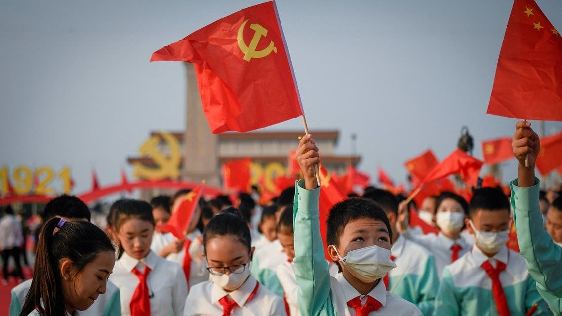 A student waves the flag of Communist Party of China before the celebrations marking the 100th anniversary of the founding of the Communist Party of China in Beijing on July 1, 2021. (AFP)