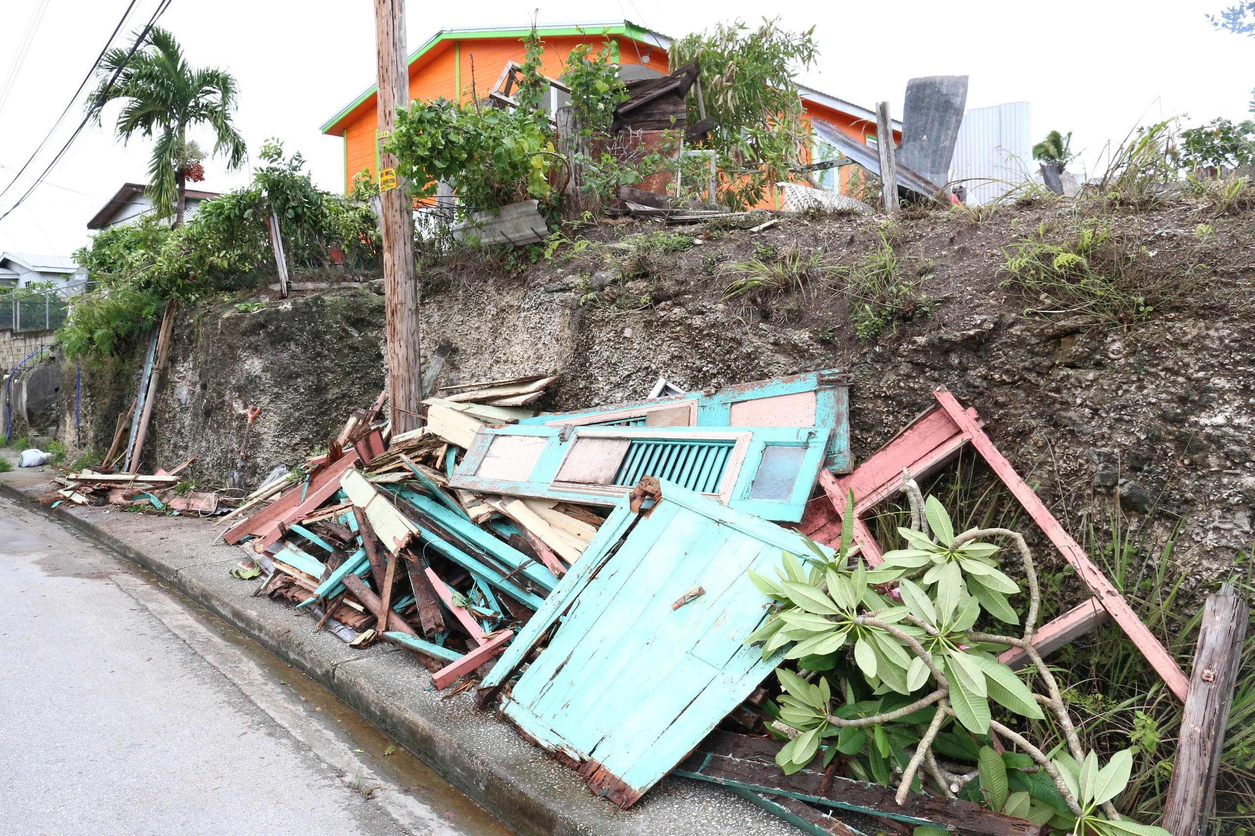 Debris from a house lie next to a road after strong winds of Hurricane Elsa passed St. Michael, Barbados July 2, 2021. (Reuters)