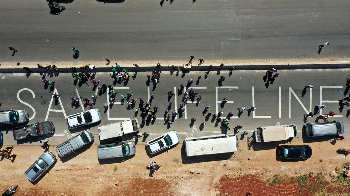 A human chain is formed calling for maintaining a UN resolution authorizing the passage of humanitarian aid into Idlib through the Bab al-Hawa border crossing with Turkey on July 2, 2021. (AFP)