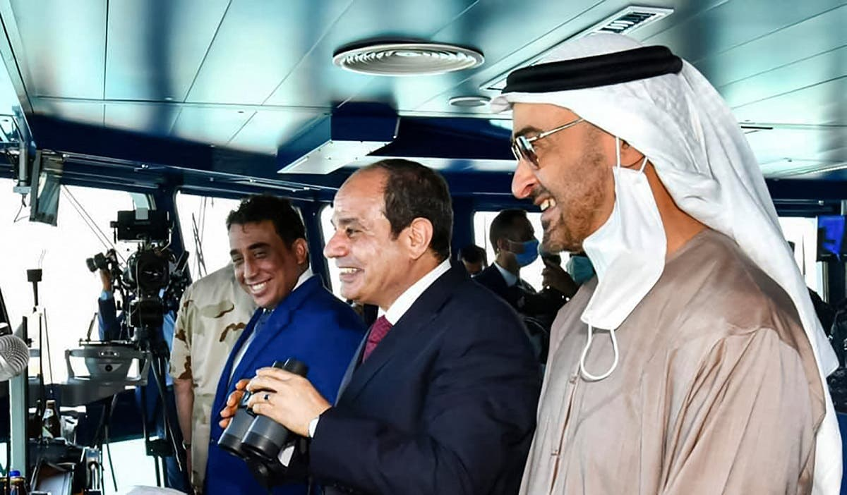 Egypt's President Sisi (C), accompanied by Abu Dhabi Crown Prince Sheikh Mohammed bin Zayed (R), standing in a control tower during the inauguration of the naval base in Gargoub on July 3, 2021, in Egypt's northwestern Mediterranean coastal city of Masra Matruh. (Egyptian Presidency/AFP)