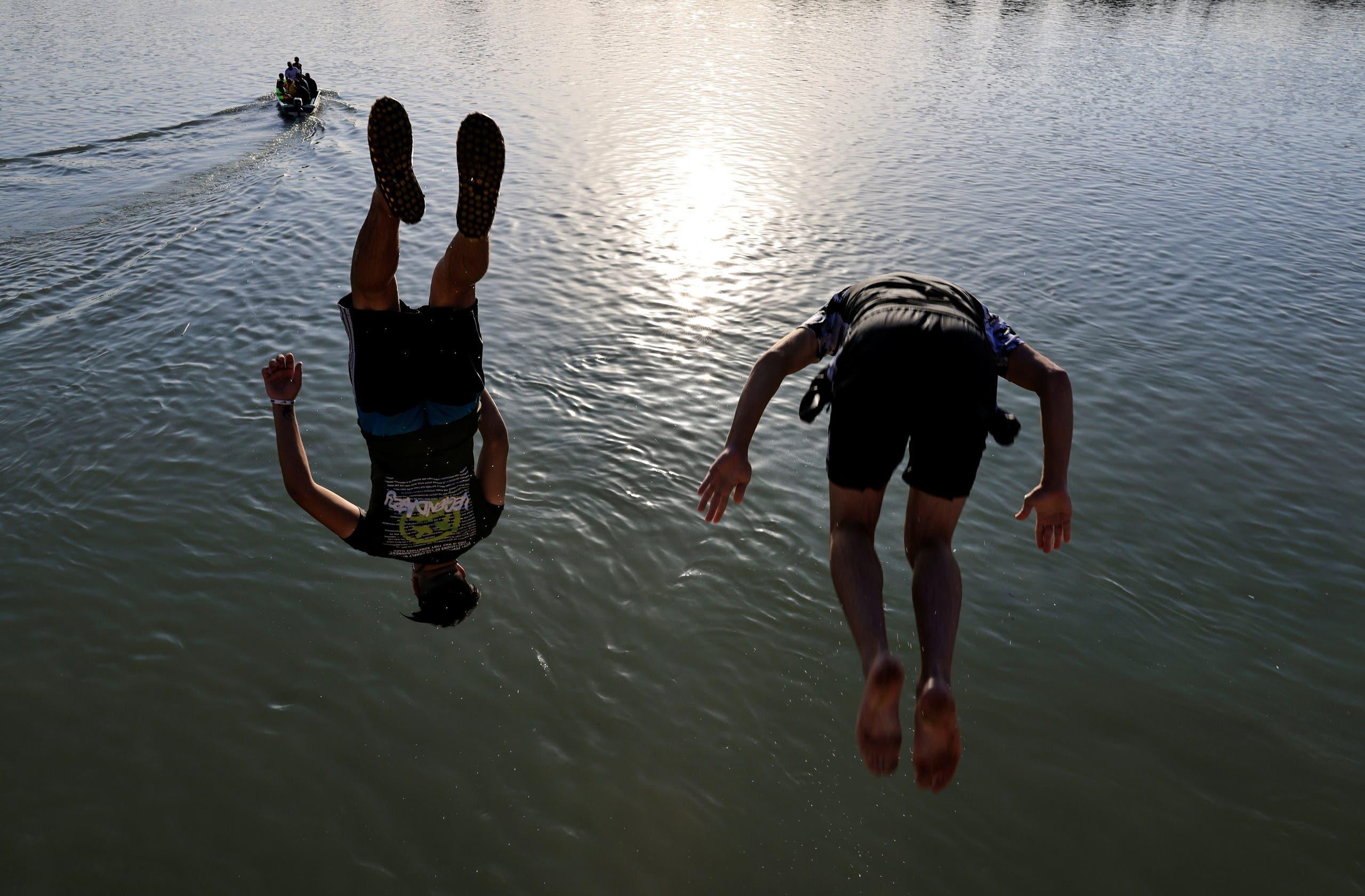 عراقيون يلجأون إلى الأنهر والمياه هربا من حر الصيف وسط انقطاع الكهرباء (رويترز)